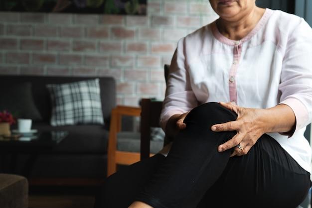 Hogere vrouw die aan kniepijn thuis lijdt, gezondheidsprobleem