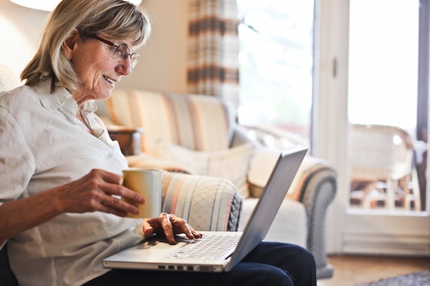 Hogere vrouw die aan laptop werkt