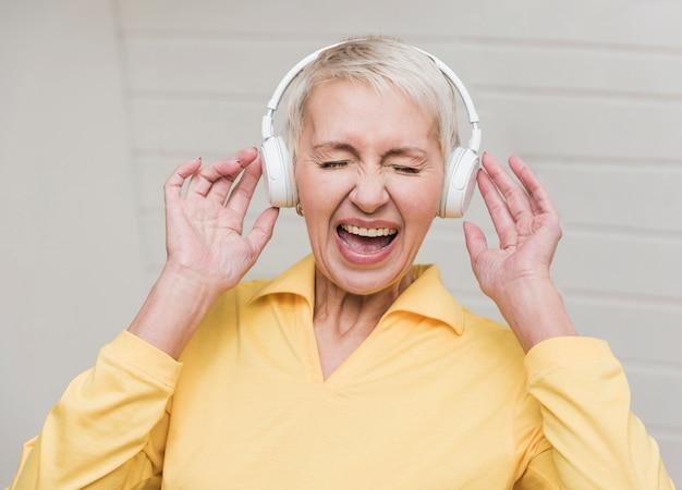 Hogere vrouw die aan luide muziek luistert