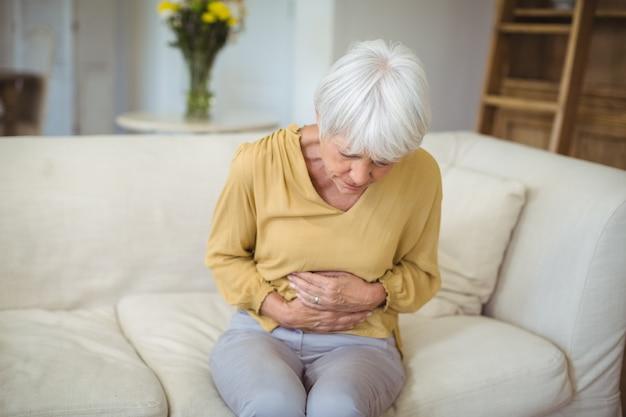 Hogere vrouw die aan maagpijn lijdt in woonkamer