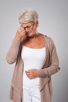 Hogere vrouw die aan sterke hoofdpijn lijdt
