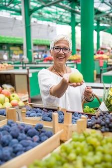 Hogere vrouw die appelen op markt koopt