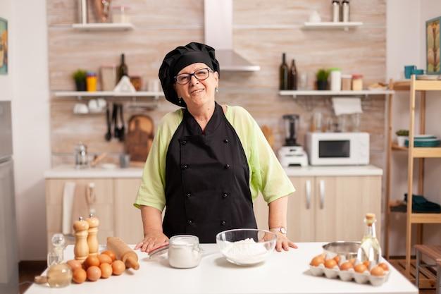 Hogere vrouw die bakkersuniform draagt in huiskeuken die bij camera glimlacht. gepensioneerde bejaarde bakker in keukenuniform die gebakingrediënten voorbereidt op houten tafel klaar om zelfgemaakt lekker brood te koken.