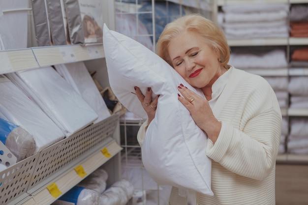 Hogere vrouw die bij de meubilairopslag winkelt