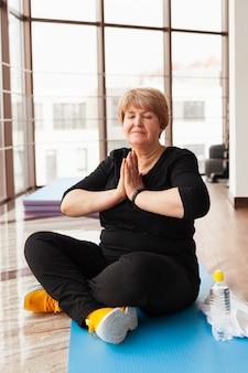 Hogere vrouw die bij gymnastiek yoga doet