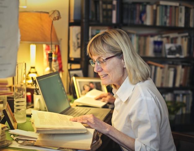 Hogere vrouw die bij haar bureau werkt
