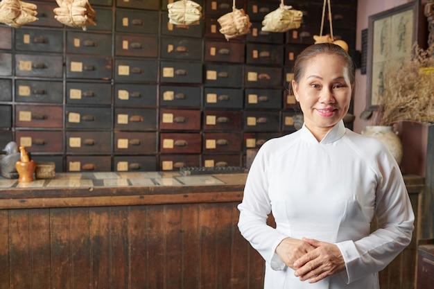Hogere vrouw die bij traditionele chinese apotheek werkt