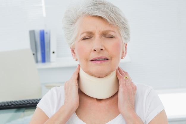 Hogere vrouw die cervicale kraag in medisch bureau draagt