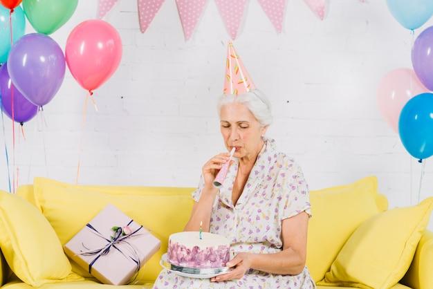 Hogere vrouw die de blazende partijhoorn van de verjaardagscake bekijkt