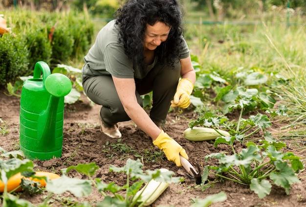 Hogere vrouw die de gewassen geeft
