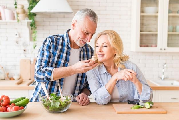Hogere vrouw die de paddestoelgreep door haar echtgenoot in de keuken ruikt