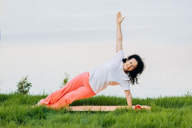 Hogere vrouw die de zijplank van yogaasana doen openlucht. . yoga