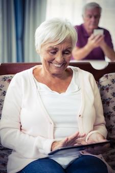 Hogere vrouw die digitale tablet gebruikt