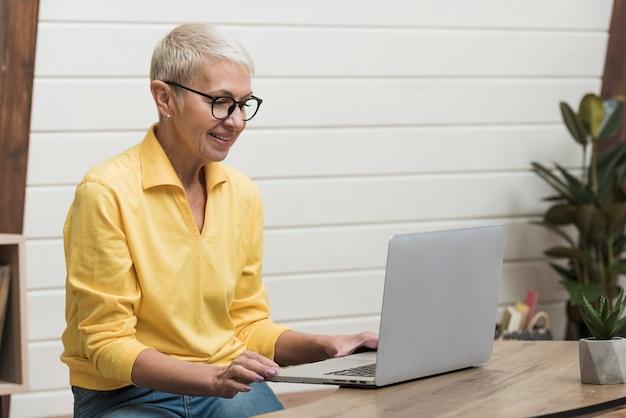 Hogere vrouw die door internet op haar laptop kijkt