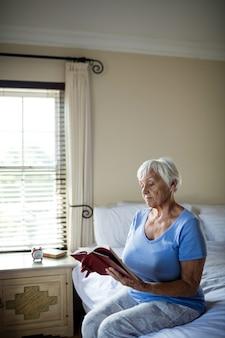 Hogere vrouw die een boek in de slaapkamer thuis leest