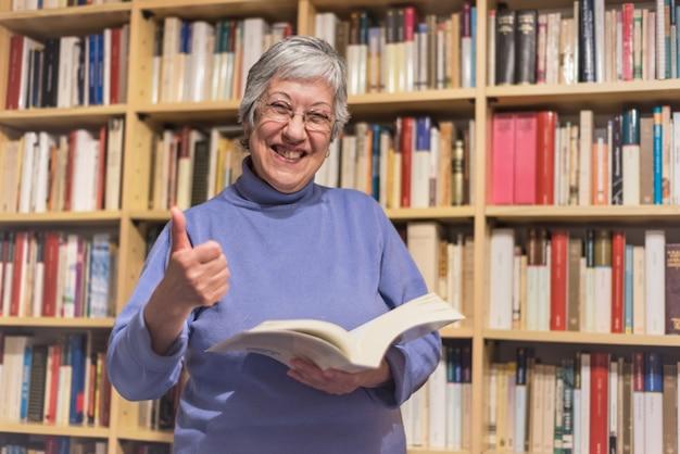 Hogere vrouw die een boek thuis leest