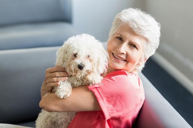 Hogere vrouw die een hond houdt