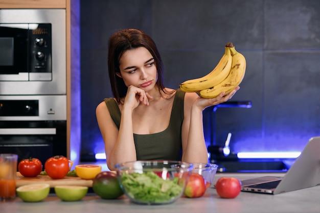 Hogere vrouw die een rotte banaan binnen houdt