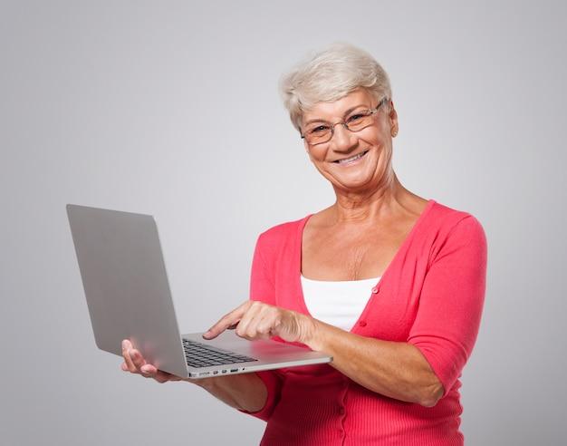Hogere vrouw die eigentijdse laptop met behulp van