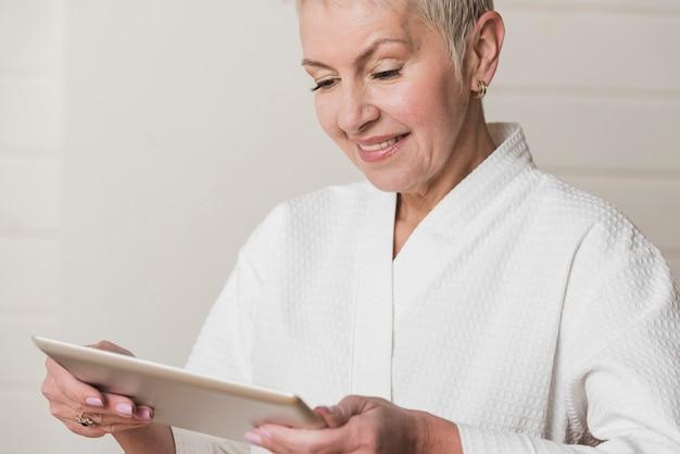 Hogere vrouw die gelukkig haar tablet bekijkt