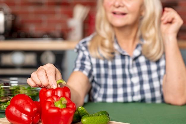 Hogere vrouw die gezond voedsel kookt