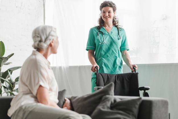 Hogere vrouw die glimlachende vrouwelijke verpleegster met rolstoel bekijkt