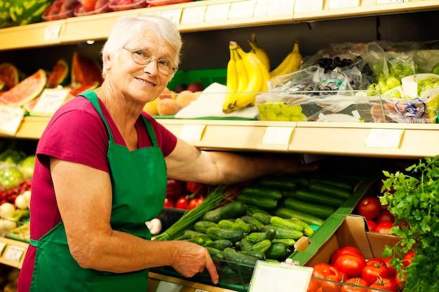 Hogere vrouw die groenten op plank schikt