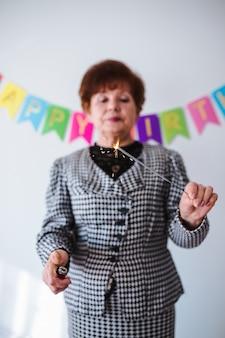 Hogere vrouw die haar birthay thuis viert