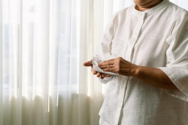 Hogere vrouw die haar handen met wit zacht papieren zakdoekje schoonmaakt. geïsoleerd op een witte tafels