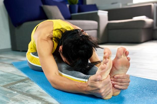 Hogere vrouw die haar lichaam op een yogamat uitrekt.