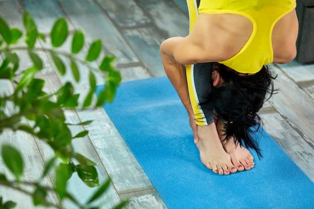 Hogere vrouw die haar lichaam, yoga thuis uitrekt.