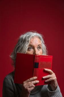 Hogere vrouw die haar mond behandelen met boek tegen rode achtergrond