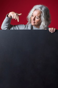 Hogere vrouw die haar vinger naar beneden op leeg zwart aanplakbiljet tegen rode achtergrond richt