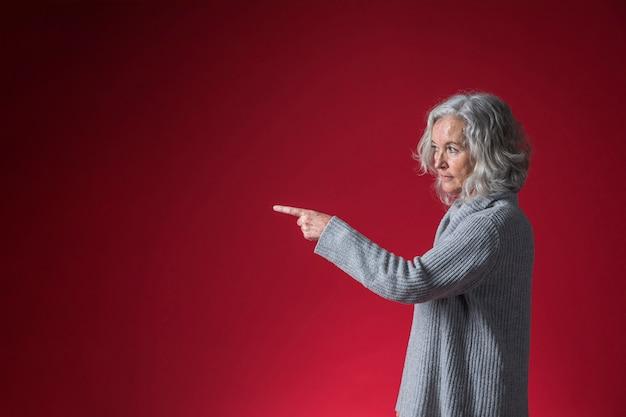 Hogere vrouw die haar vinger richt op iets tegen rode achtergrond