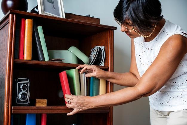Hogere vrouw die het boekenrek schoonmaakt