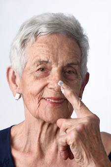 Hogere vrouw die huidroom of vochtinbrengende crème toepast op haar gezicht