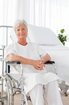 Hogere vrouw die in haar rolstoel de camera bekijkt