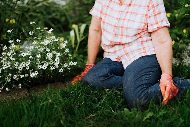 Hogere vrouw die in haar tuin rust