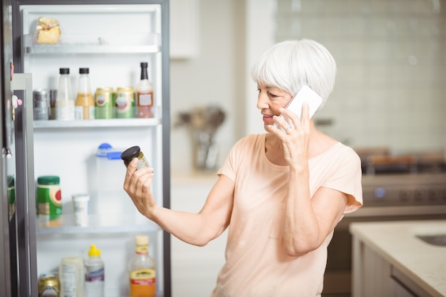 Hogere vrouw die kruik bekijkt terwijl het spreken op mobiele telefoon in keuken