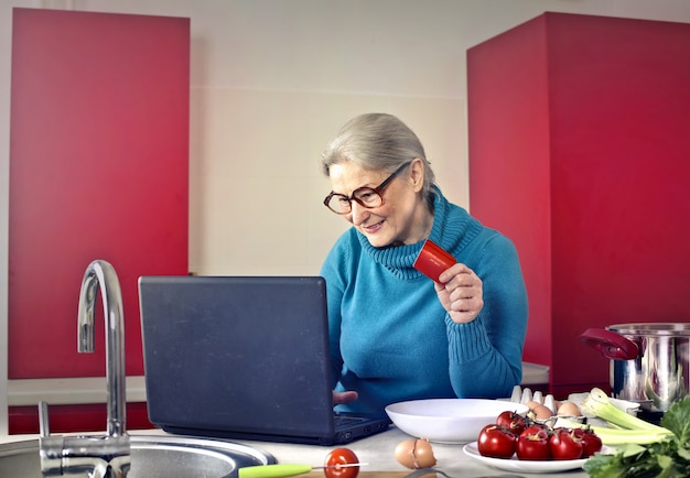 Hogere vrouw die laptop in de keuken met behulp van