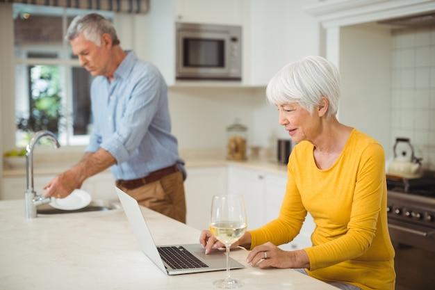 Hogere vrouw die laptop in keuken met behulp van