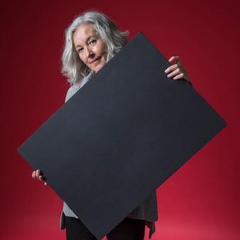 Hogere vrouw die leeg zwart aanplakbiljet houden die zich tegen rode achtergrond bevinden
