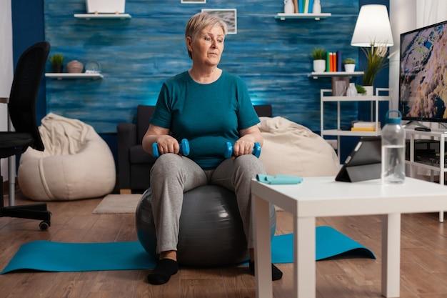 Hogere vrouw die lichaamsspieren uitoefent die wapensoefening doen die op zwitserse bal zitten