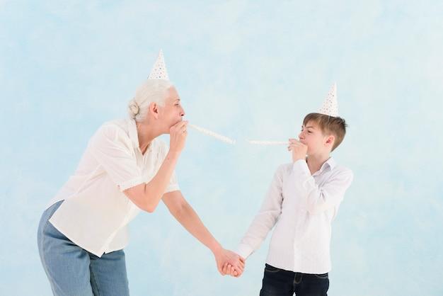 Hogere vrouw die met haar kleinzoon met partijhoed en hoorn op blauwe oppervlakte geniet van