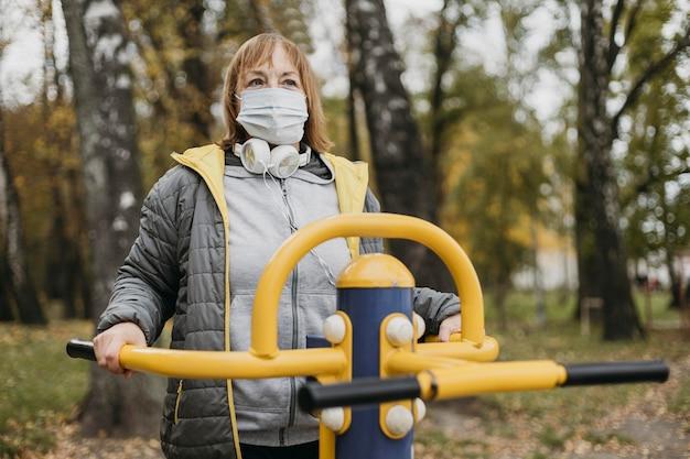 Hogere vrouw die met medisch masker in openlucht uitwerkt