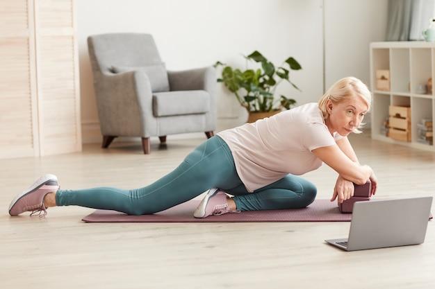 Hogere vrouw die oefeningen op oefeningsmat doet en deze oefeningen op laptop thuis bekijkt