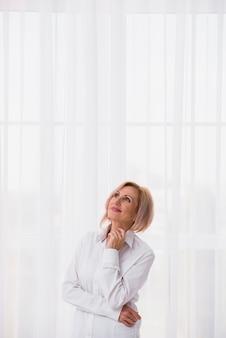 Hogere vrouw die omhoog met exemplaarruimte kijkt
