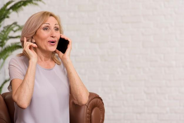 Hogere vrouw die op de telefoon met exemplaarruimte spreekt