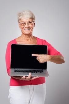 Hogere vrouw die op eigentijdse laptop toont