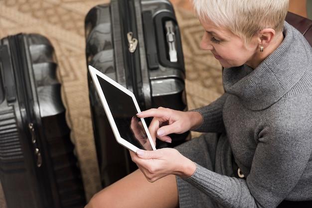Hogere vrouw die op haar tablet kijkt